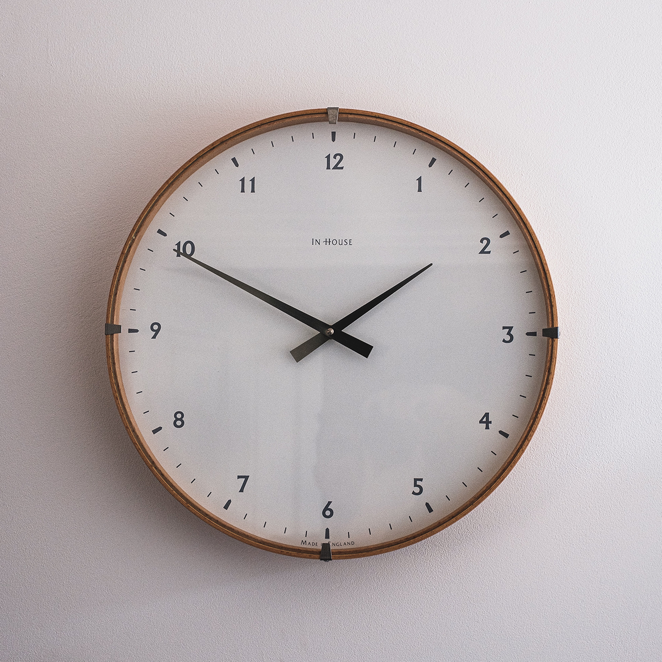 Analog clock mounted on the wall reading one fifty in the afternoon.