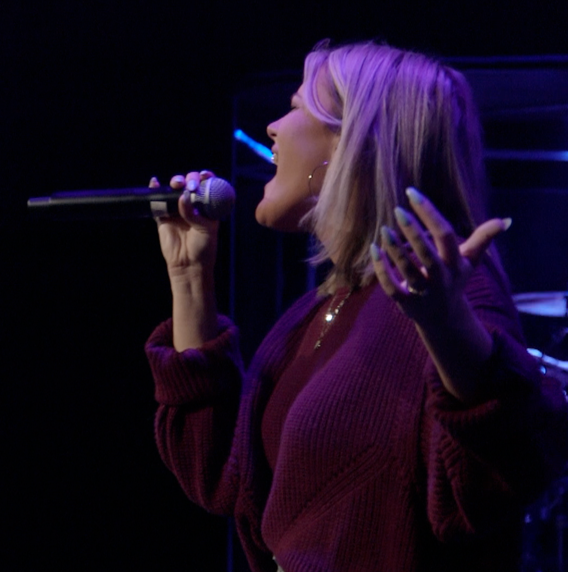 Woman singing with microphone in her hand.