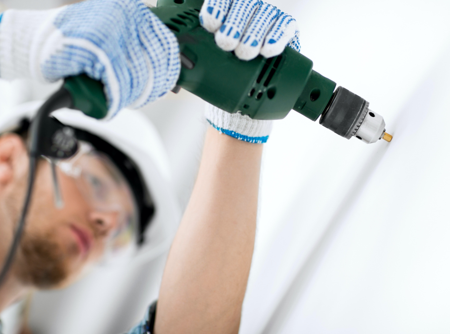 A Sonus Certified Pro Installer hangs an acoustic panel with a drill