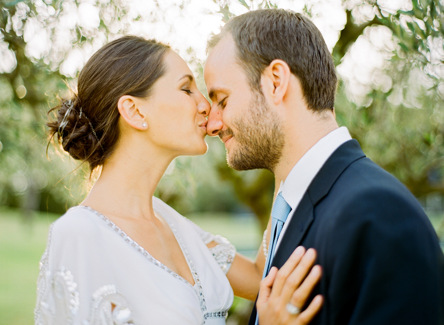 Portrait of bride and groom kissing outside on a sunny day