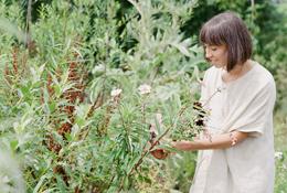 A portrait of a woman gathering flowers in a garden