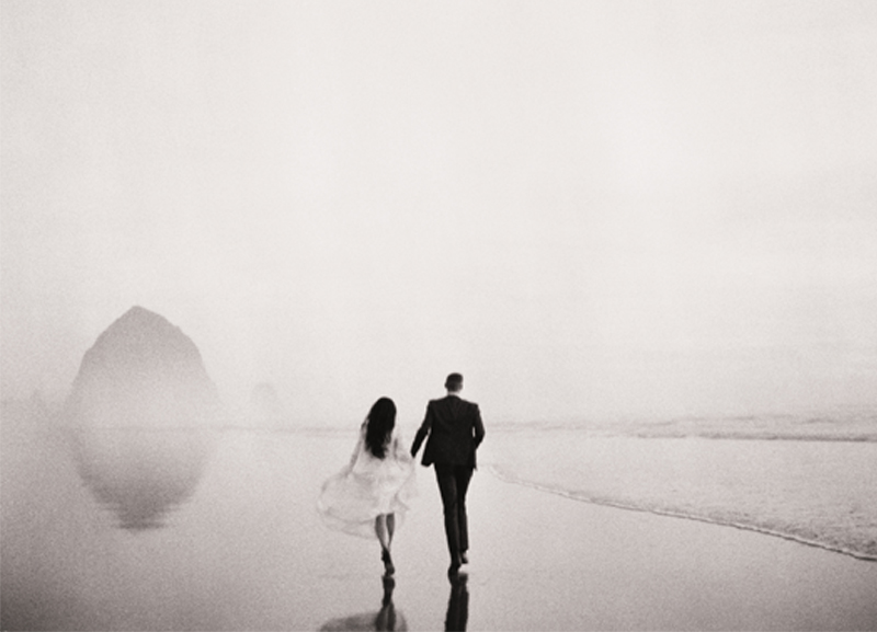 Black and white portrait of a bride and groom walking on the beach
