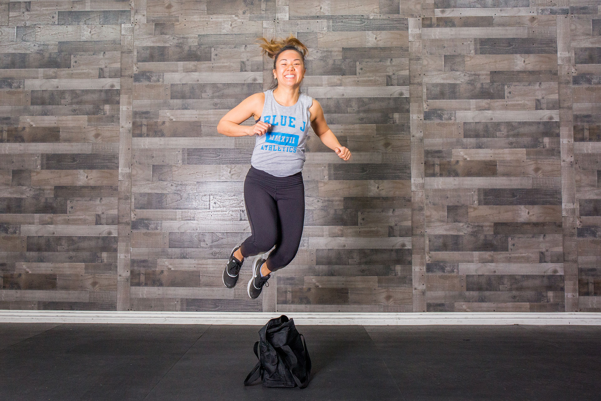 Janet, a Gymparty coach, jumping laterally over a black bag on the floor and smiling