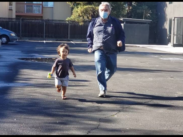 Bruce, a 69 year old Gymparty member, running in the parking lot with his 2 year old grandson
