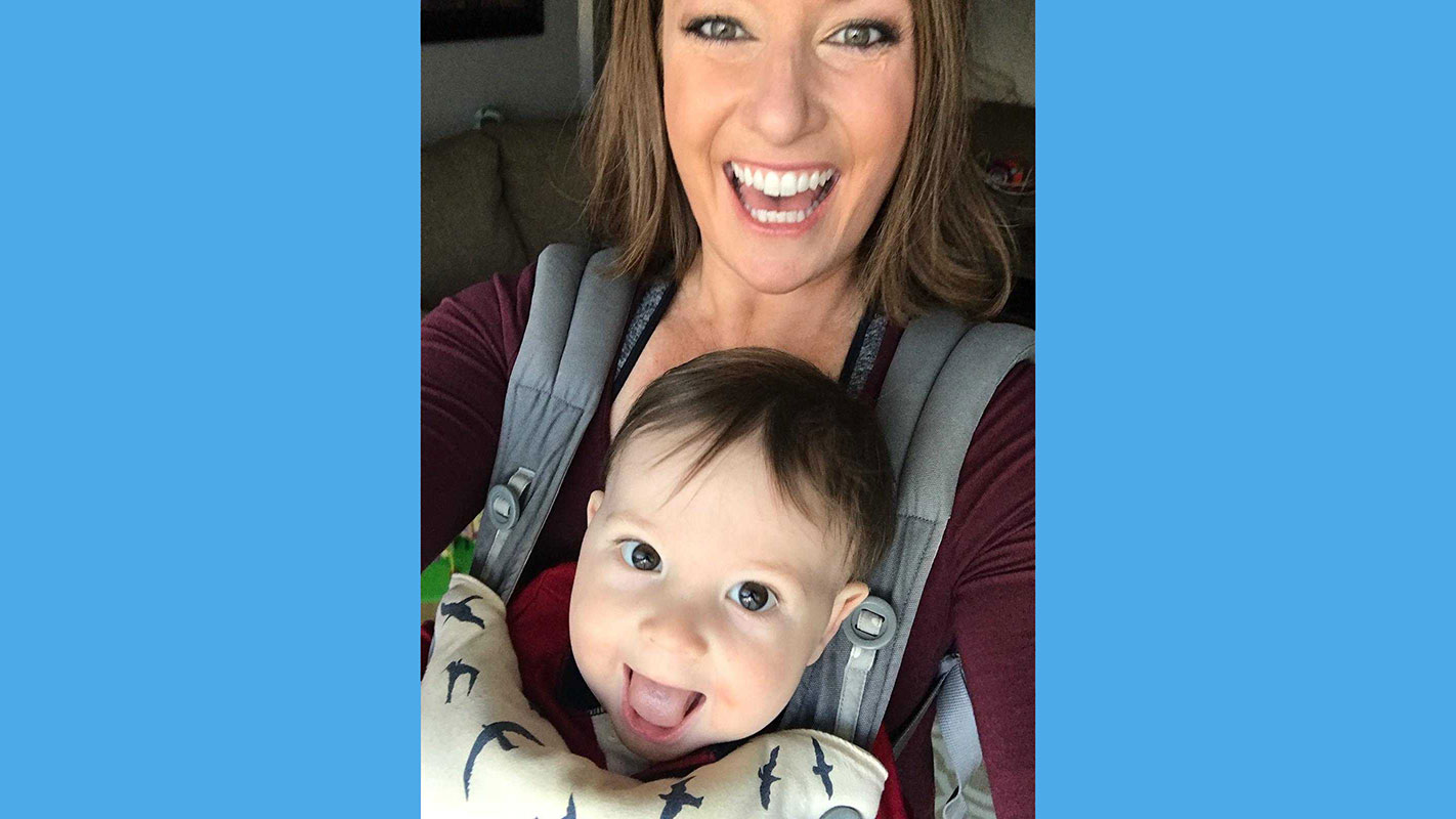 Kristin, a Gymparty member, wearing her baby in a carrier.