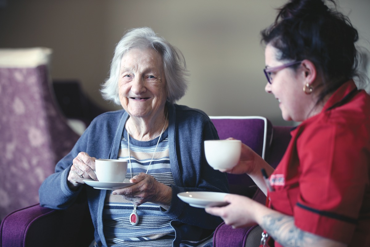 A Mears employee drinking a cup of tea with an elderly female
