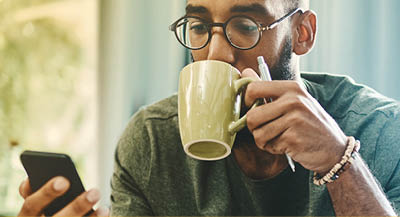Man wearing glasses drinking coffee and holding a pen