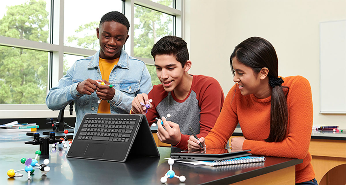 Three children in a classroom using a computer.