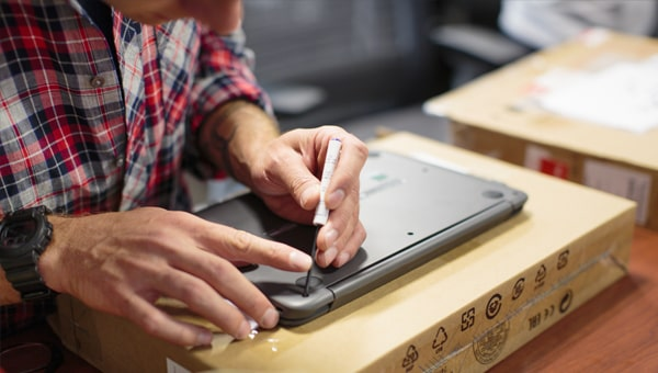 a tech removing the rear plate of a laptop