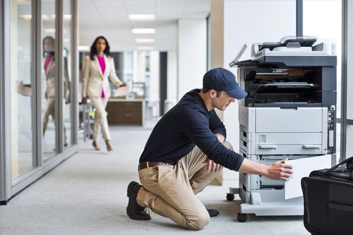tech servicing a printer