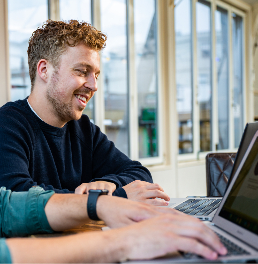 DIQQ employee smiling at laptop