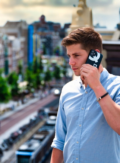 DIQQ employee holding phone to ear with Amsterdam backdrop