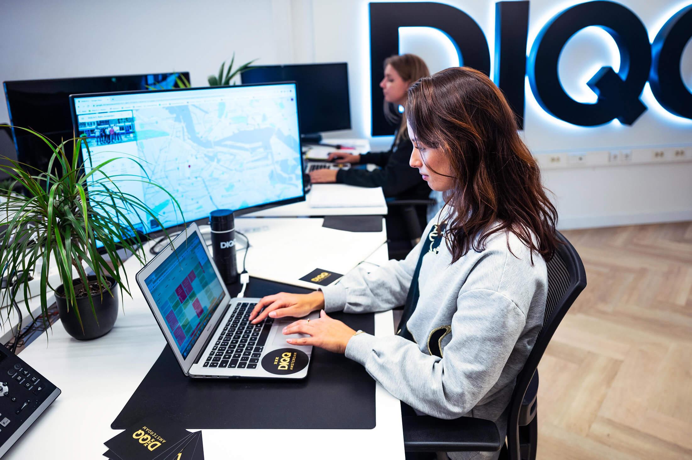2 DIQQ medewerkers zitten aan tafel met een klant inclusief koffie en laptops