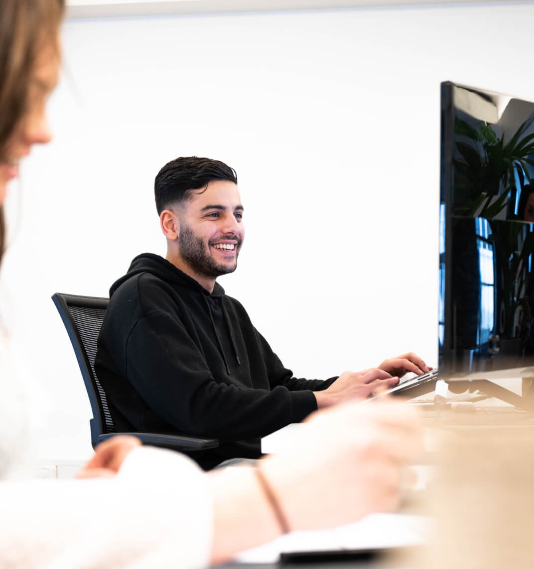 DIQQ employees looking at laptop together