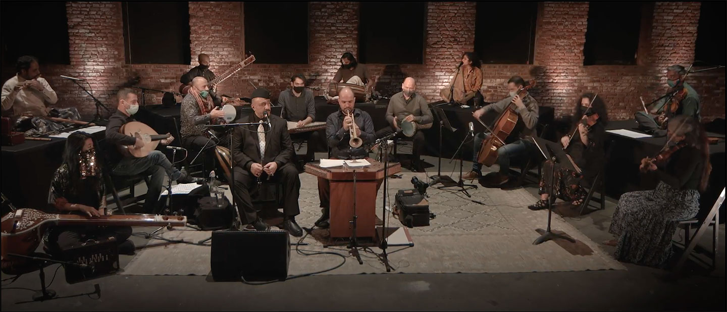 15 musicians playing a mixture of stringed instruments, percussion, and wind instruments in a semicircle on stage