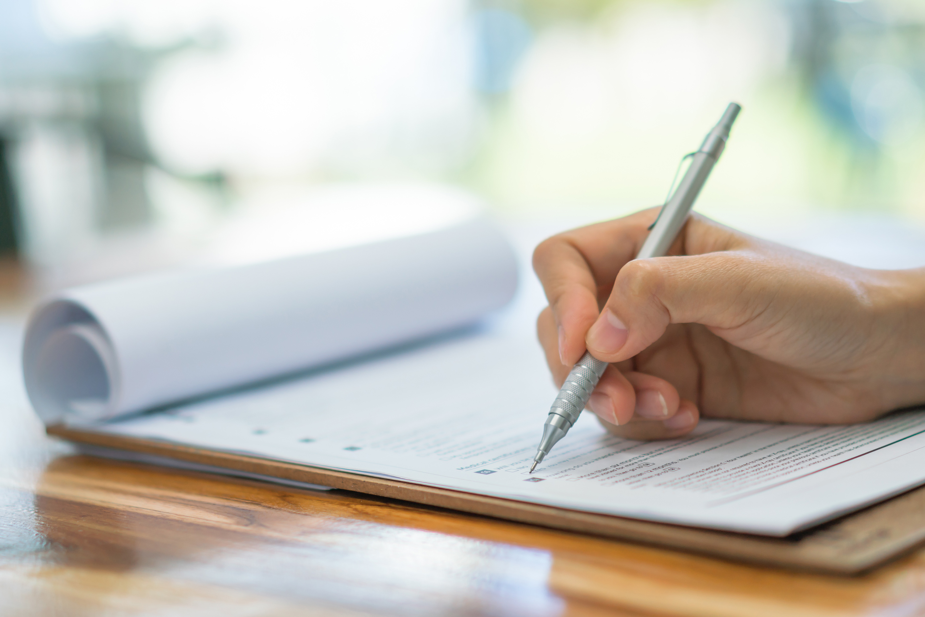 A close-up of hand writing on a notepad