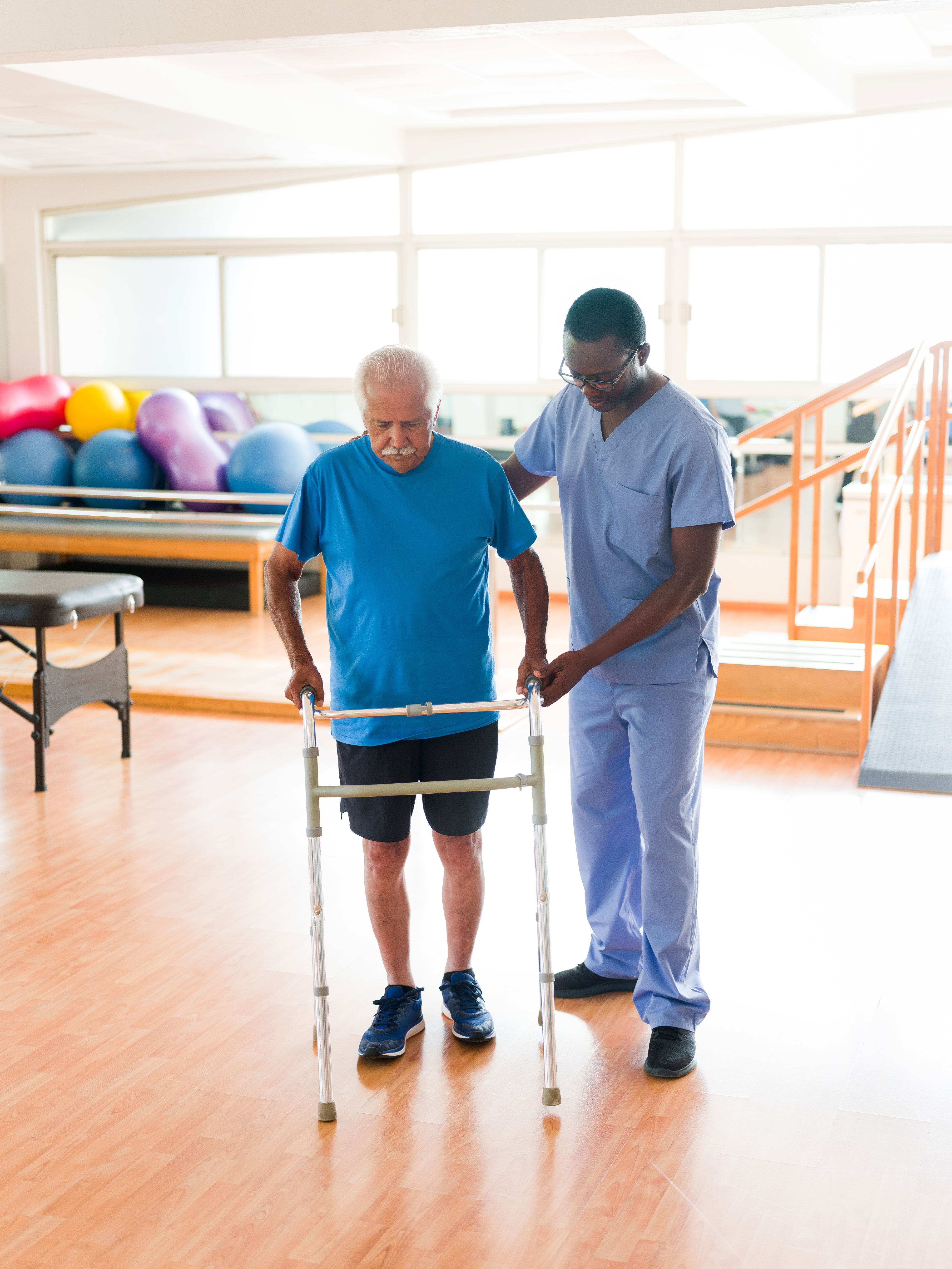 Man using walker with rehabilitation specialist