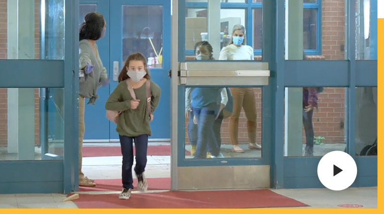 Young student exiting a school building