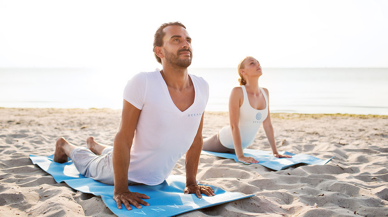 Couple doing yoga on the beach