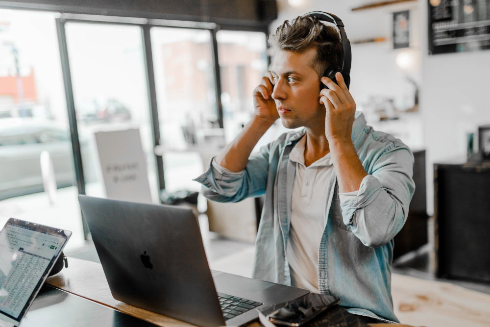 A man wearing a headset listening to the Derek Prince Legacy Radio podcast on his laptop