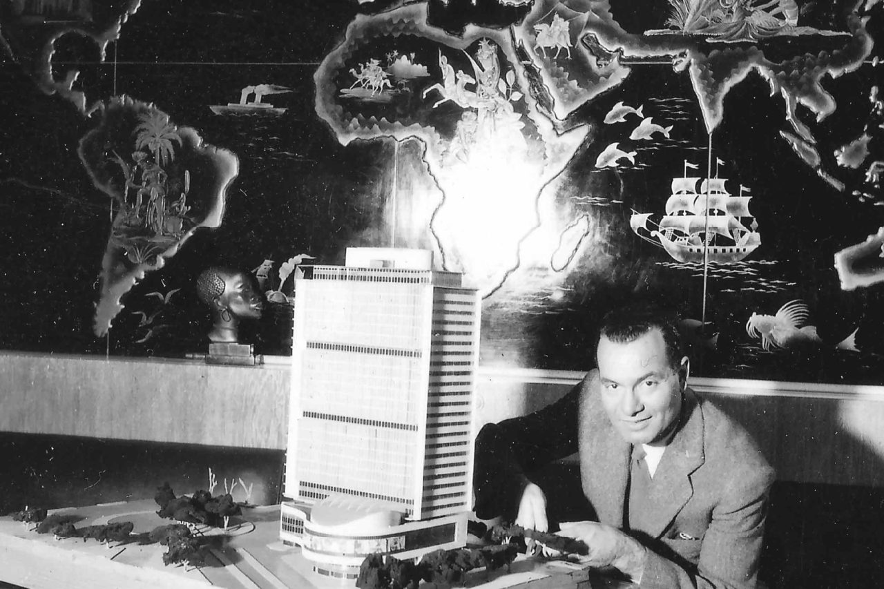 A black and white photograph of architect Sayed Karim posing at his home office with a model of his unbuilt Hotel Nefertiti, circa 1960.