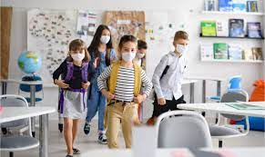 Group of children in face masks walking into a classroom.