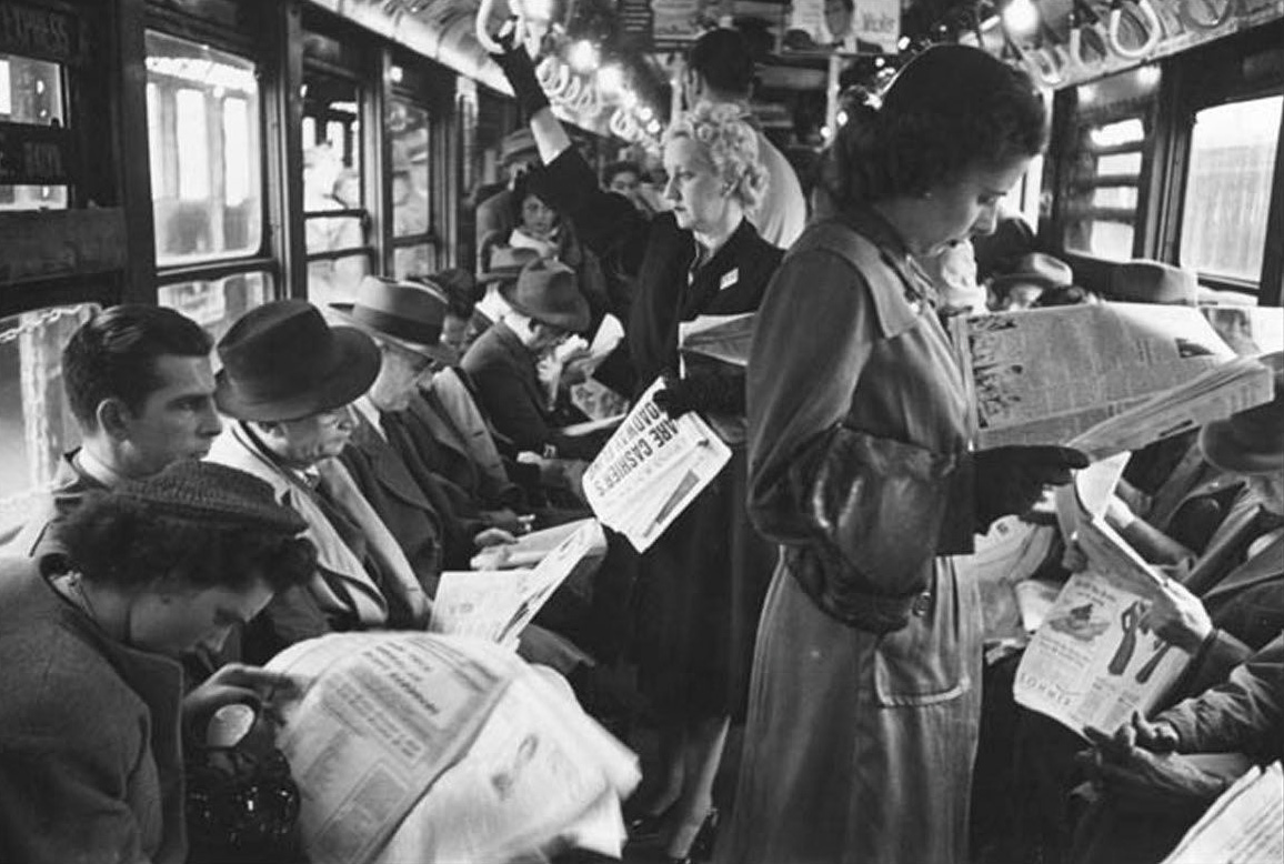 Black and white image of the inside of a 1950s NYC subway car