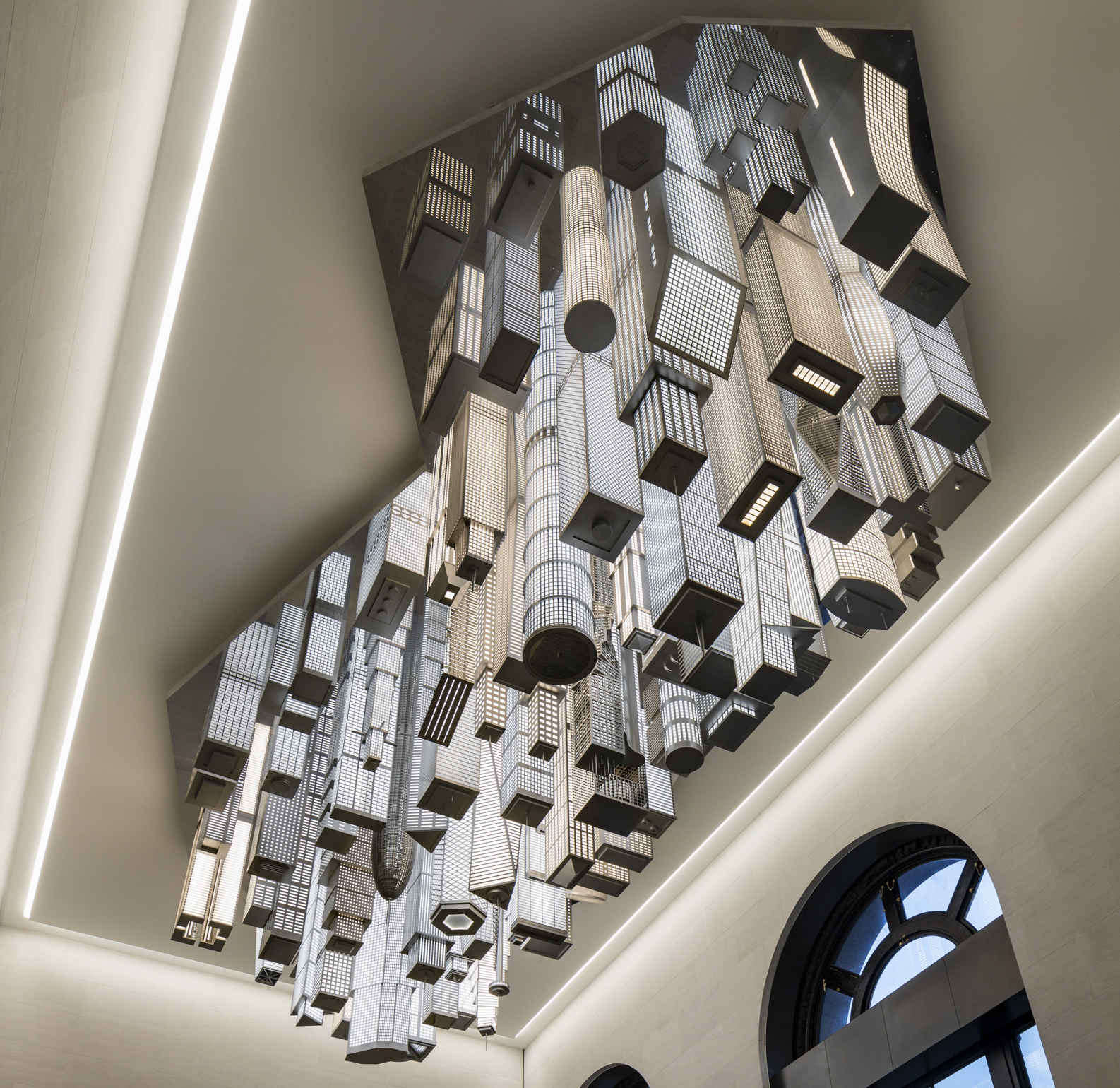 """A photograph of """"The Hive,"""" a public art work by Elmgreen & Dragnet that depicts a scaled architectural model of a global metropolis suspended from the ceiling of Moynihan Station's 31st Street Entrance Hall."""