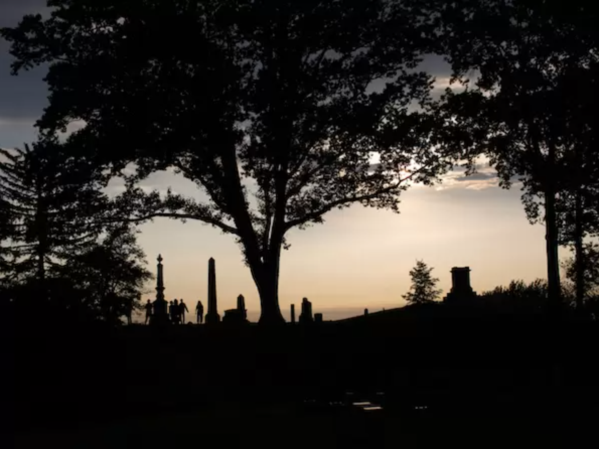 A dusk photo of headstones, trees, and the sky at Green-Wood Cemetery