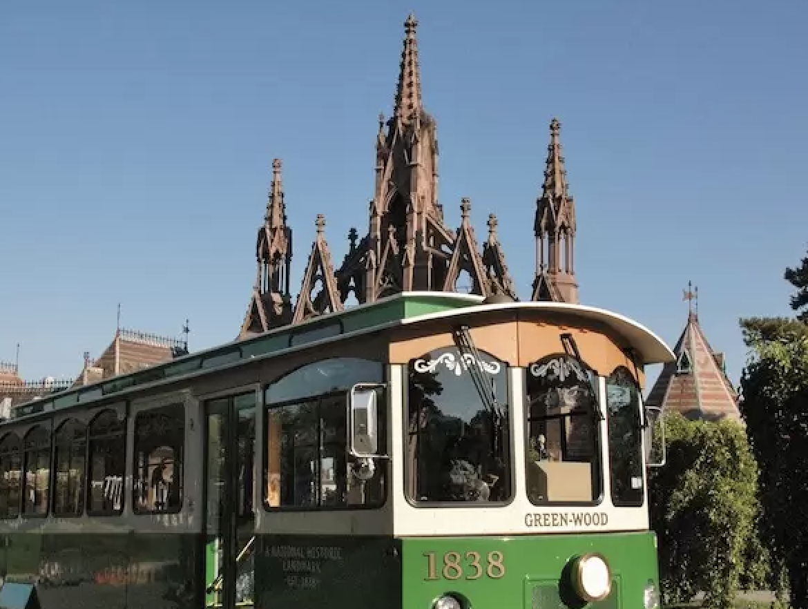 A vintage trolley in front of Green-Wood's monumental gothic gate.