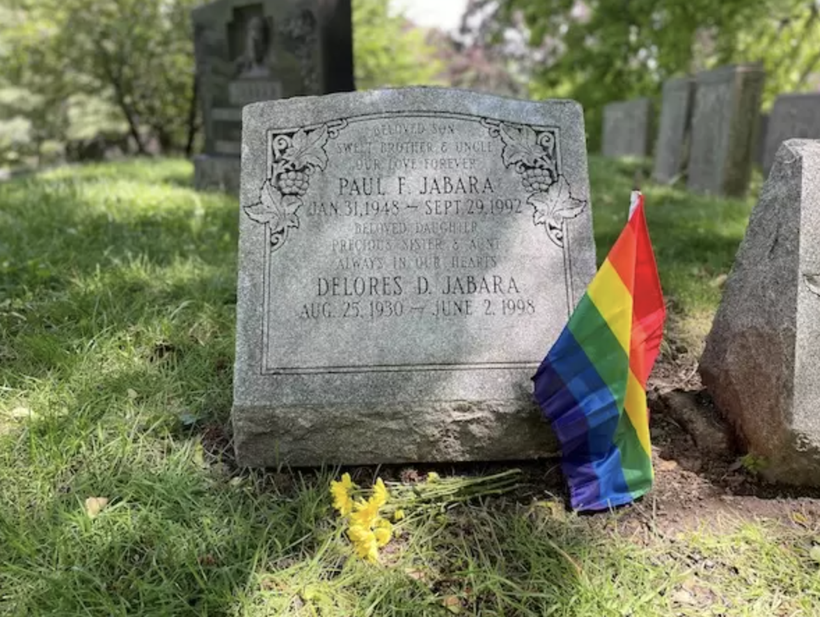 A small tombstone with a LGBT rainbow flag.