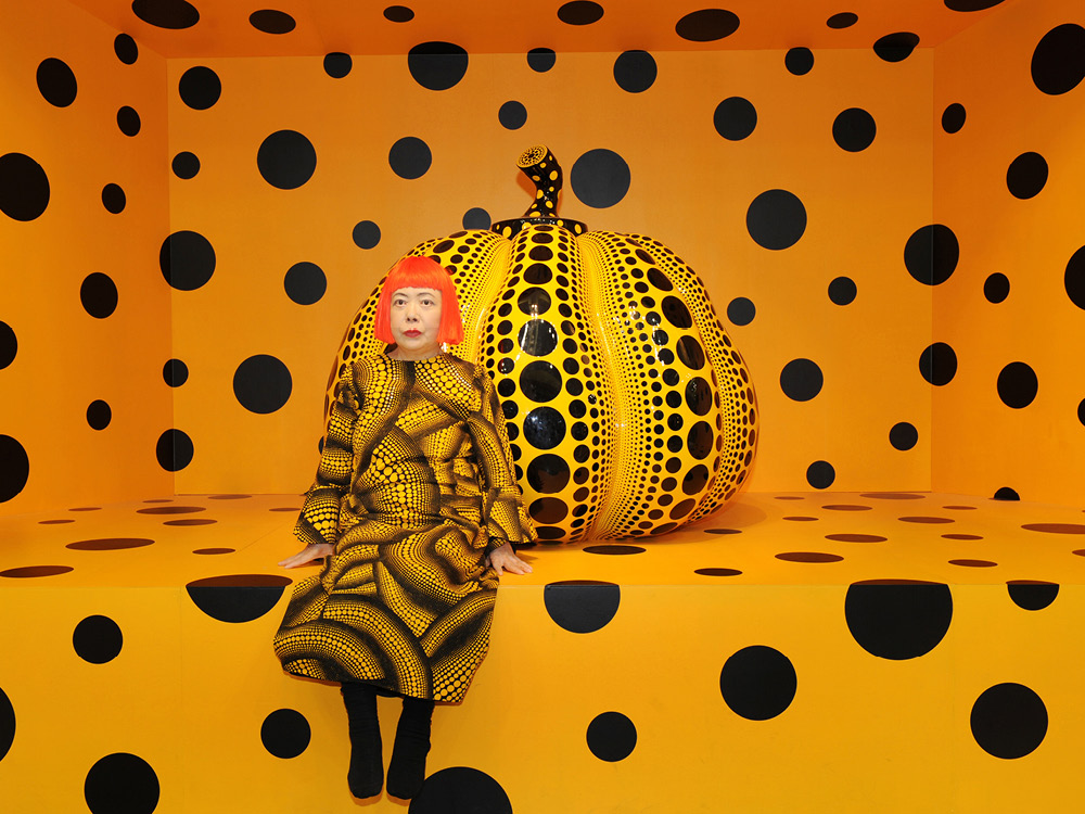 A woman sitting in front of a large pumpkin, entire scene decorated with black polka dots on orange background