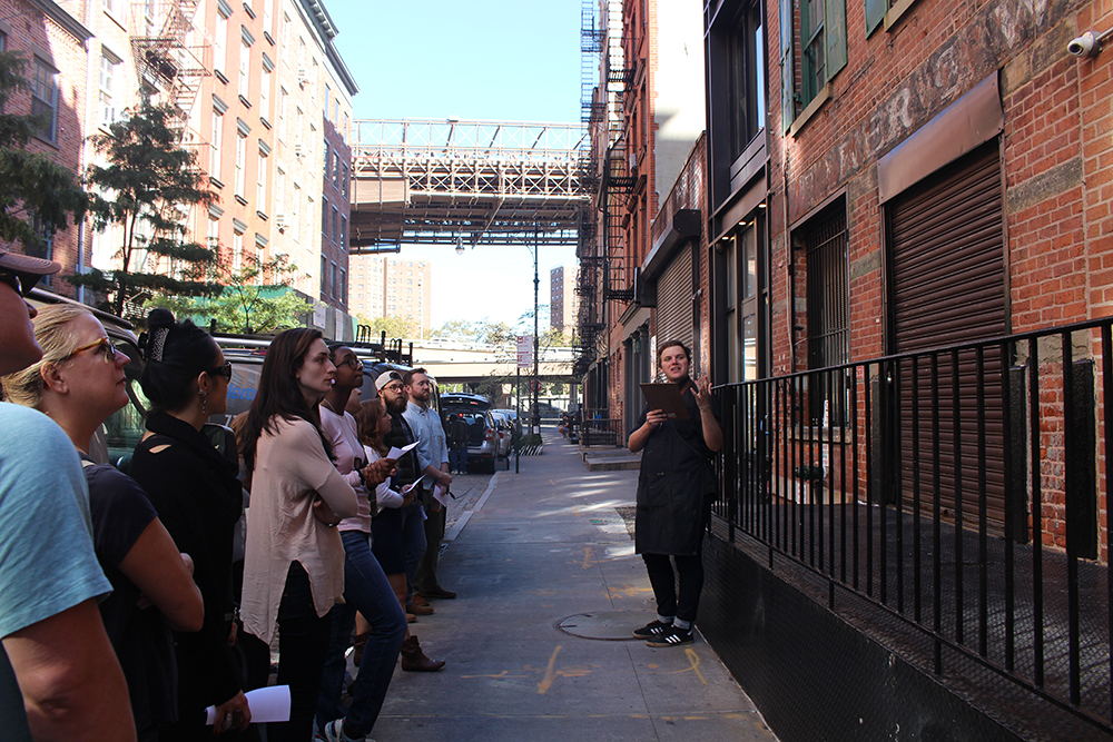 View of a street with a tour guide speaking to a group of attendees