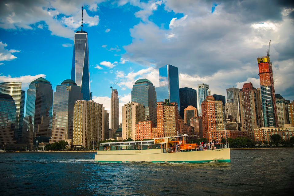 A photo of one of Classic Harbor Line's 1920s-style boats with the New York City skyline in the background.
