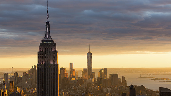 Picture of downtown Manhattan skyline with a dramatic sunset with yellows and blues.