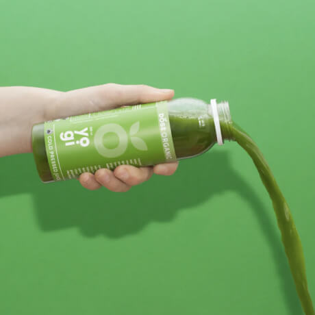 Person pouring out a drink against a green background.