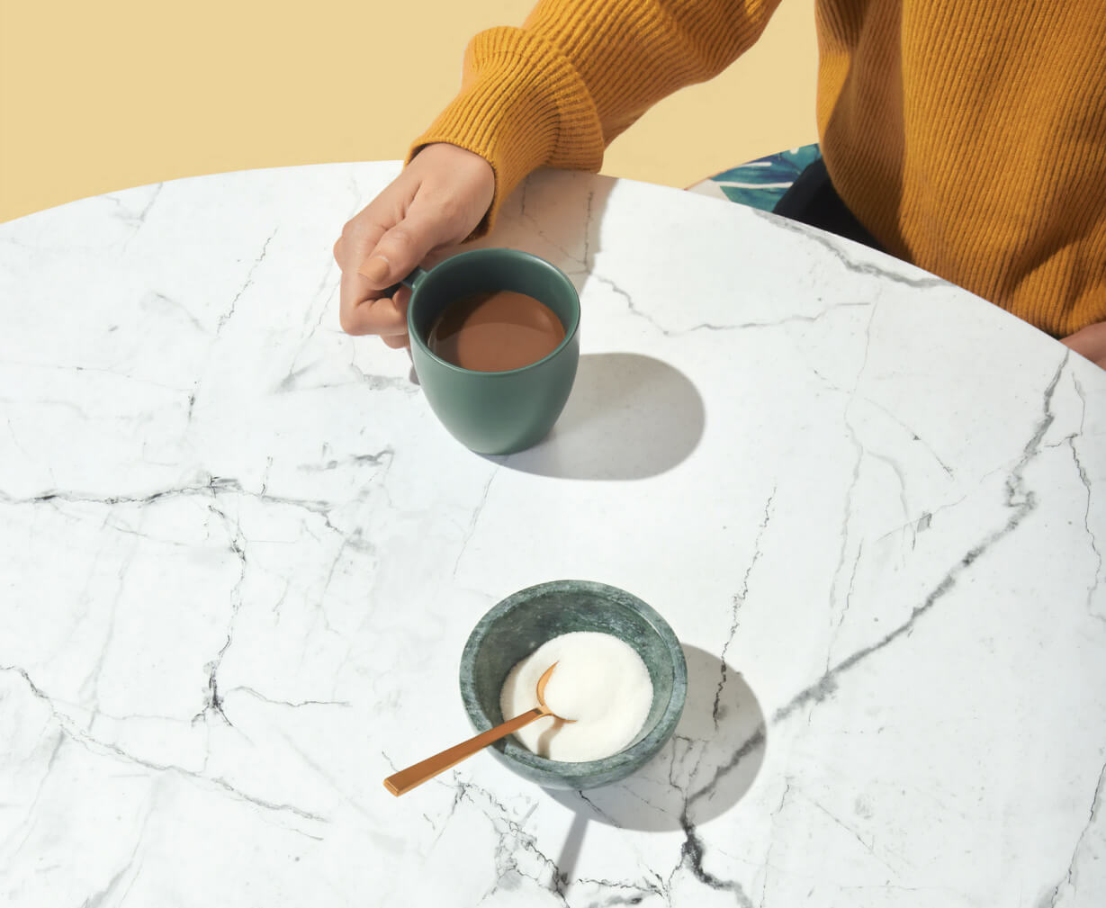 Person holding a coffee cup on a table.