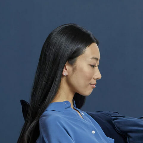 Side profile headshot of a woman in blue shirt.