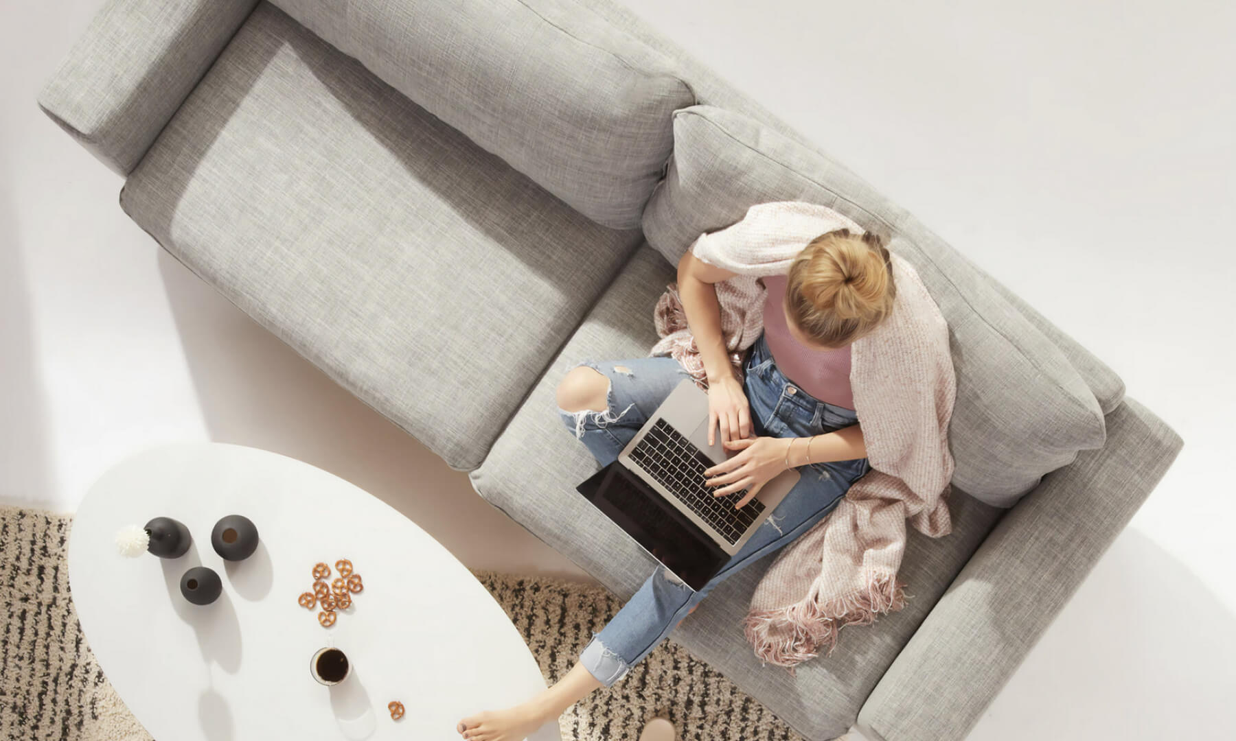 Birds eye view of a woman sitting on her couch, working on her laptop.