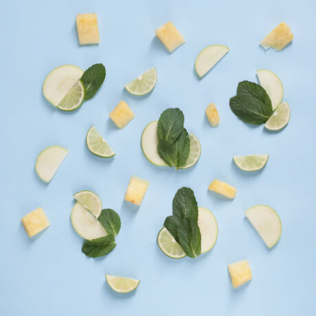 Cucumber, lime, and mint leaves spread out on a light blue background.