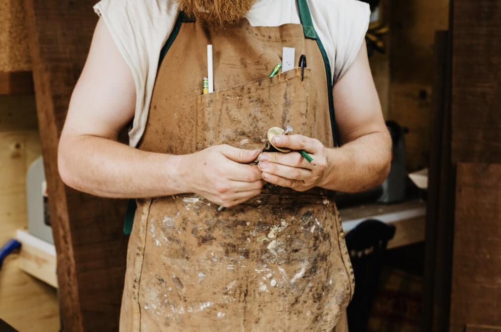 An artisan wearing a dirty apron.