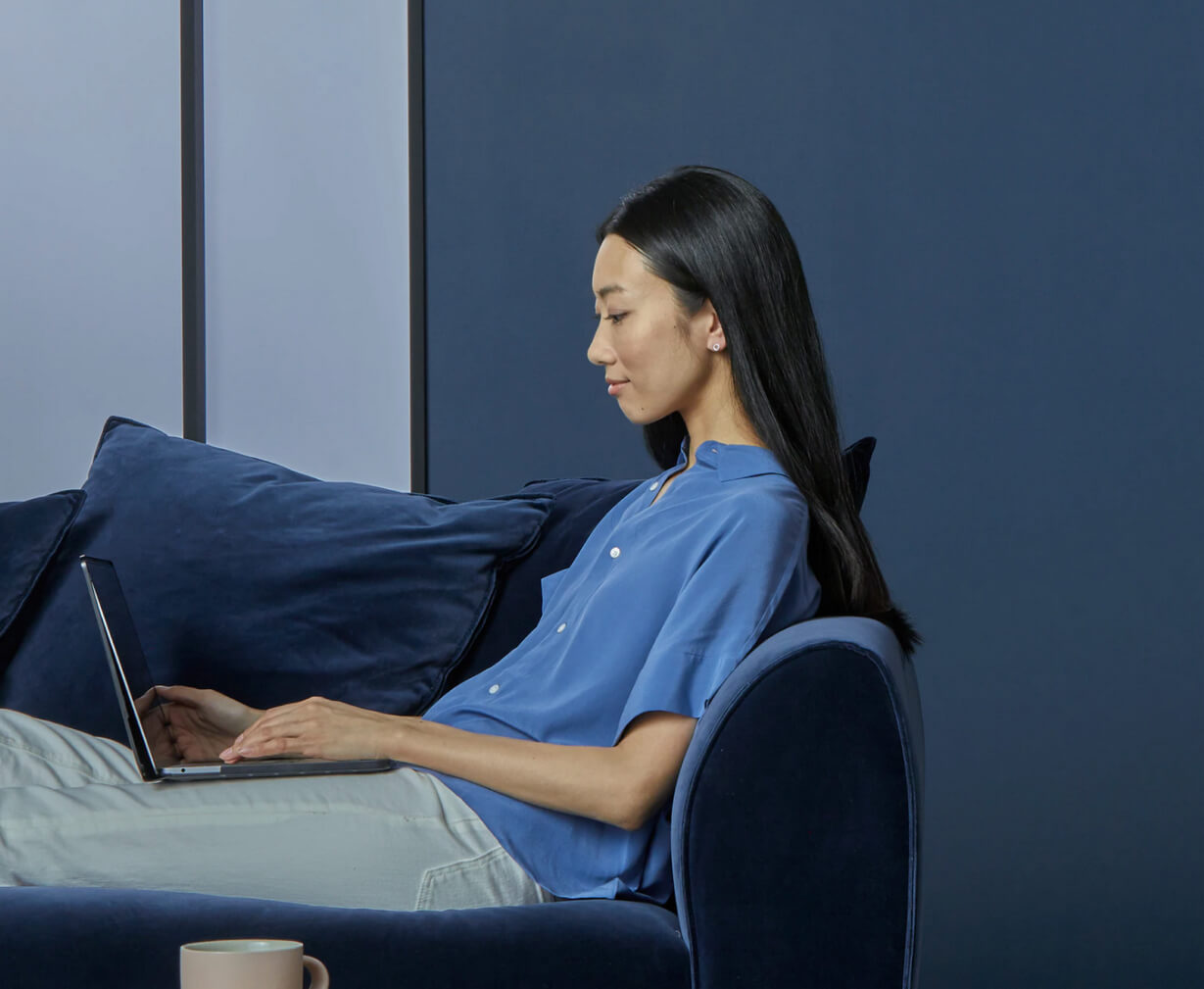 Profile of a woman wearing a blue shirt, working on her laptop.