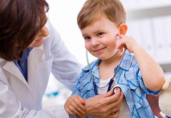 a smiling child with a doctor using a stethoscope