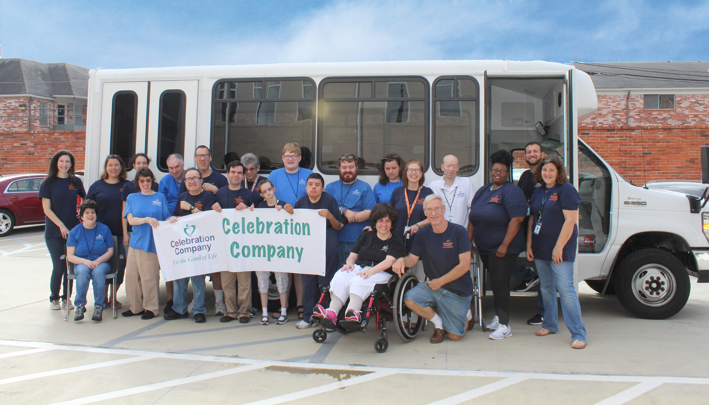 Celebration Company employees and staff pose in front of their bus