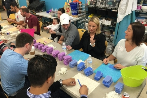 A group of volunteers work on rolling candles at Celebration Company