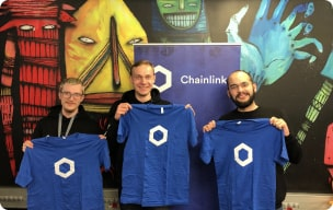 Chainlink community members holding Chainlink t-shirts