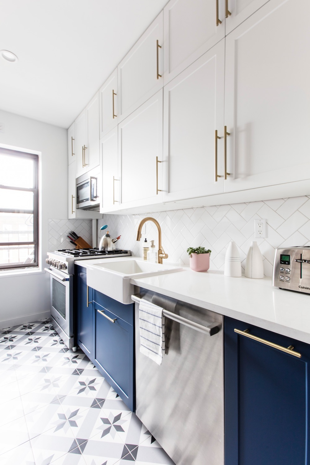 Kitchen renovation, blue and white cabinetry and gold handles