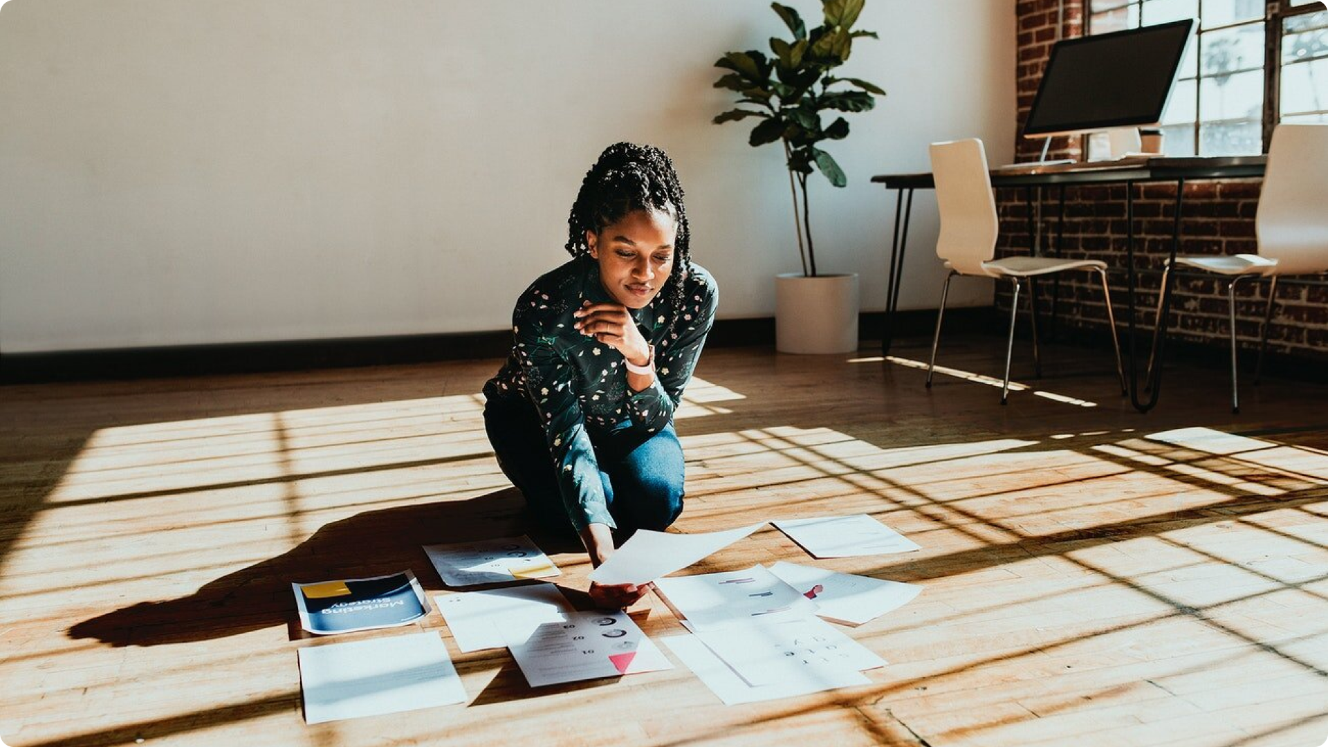 Woman looking at work and design papers on the floor in a well-lit office