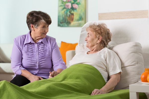 A friend comforts an old woman in a hospital bed