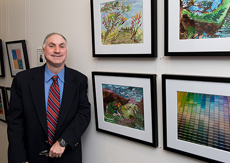 Neville standing in front of his four photographs